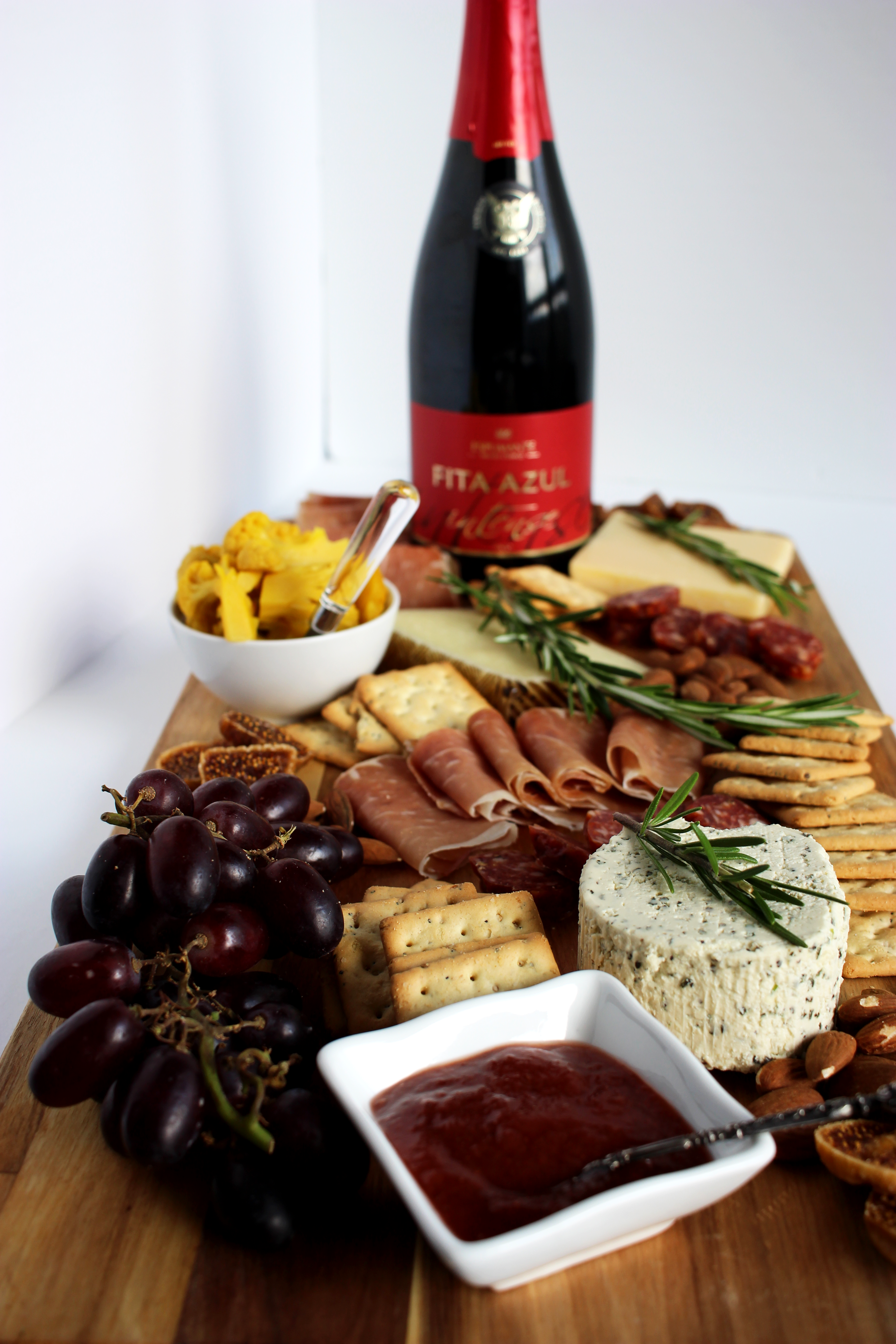 red sparkling bottle of wine with cheese charcuterie board